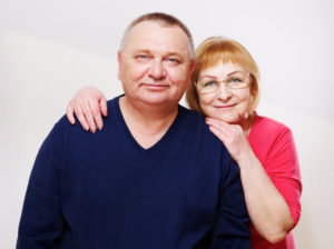 Close up portrait of middle aged couple over white background